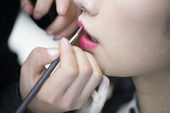 Makeup artist applying make-up to young woman Stock Photos