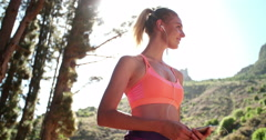 Woman runner wearing earphones selecting music on her phone - stock footage