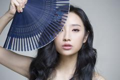 Stock Photo of Beautiful young woman with folding fan