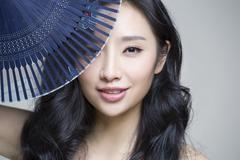 Beautiful young woman with folding fan - stock photo