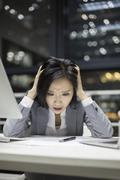 Businesswoman working late in office - stock photo