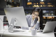 Stock Photo of Businesswoman working late in office