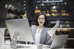 Happy businesswoman working late in office - stock photo