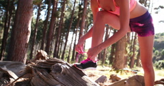 Woman trail runner fixing her shoelaces on her running shoes - stock footage