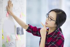 Female designer working in office Stock Photos