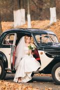 Beautiful happy bride with bouquet near retro car in autumn - stock photo
