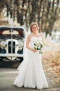 Beautiful happy bride with bouquet near retro car in autumn - stock photo