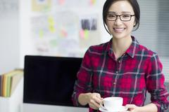 Young woman taking a coffee break - stock photo