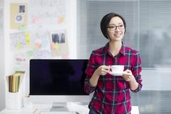 Stock Photo of Young woman taking a coffee break