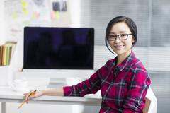 Portrait of young woman in office - stock photo