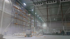 The workers on the scaffolding inside a large and modern warehouse Stock Footage