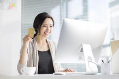 Young woman shopping online in office - stock photo