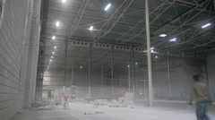 the workers on the scaffolding inside a large and modern warehouse - stock footage