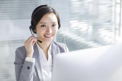 Businesswoman working in office with headset - stock photo