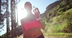 Athlete outdoors with trees drinking water from a clear bottle - stock footage