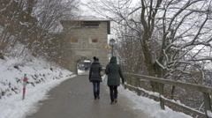 Two women walking towards an arch at Salzburg Fortress in Salzburg Stock Footage