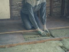 Young woman laying insulation in loft - stock photo