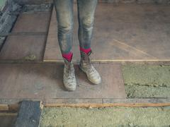 Feet and legs of worker by insulation Stock Photos