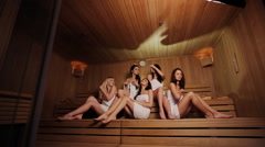 Sauna spa therapy beautiful young people group in warm wood room white towel Stock Footage