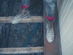 Feet of worker standing on floor joists - stock photo