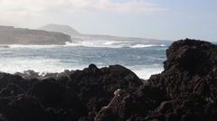 Looking out to sea over volcanic rocks, with misty sea spray Stock Footage