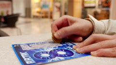 Close up woman scratching lottery ticket called electric inside shopping mall - stock footage