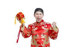 Young groom in Tang suit holding a embroider ball - stock photo