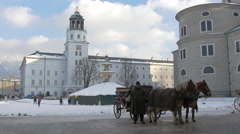 Stock Video Footage of Beautiful view of a horse carriage and a man standing near Salzburg Cathedral