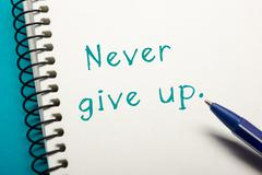 Never give up message - Office table top view. Notepad with text and pen Stock Photos