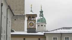 Stock Video Footage of Beautiful view of a clock tower and a spire of Salzburger Dom in Salzburg