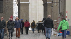 People walking and a woman begging near Salzburg Cathedral in Salzburg Stock Footage