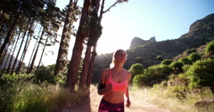Fit athletic woman running on a sunlit mountain dirt path - stock footage