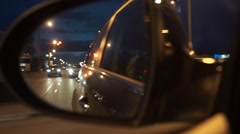 Side mirror rear view from moving car at night Stock Footage