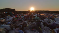 Sunset over landfill site of domestic waste jib shot Stock Footage