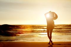 Silhouette of young woman walking on beach from behind Stock Photos