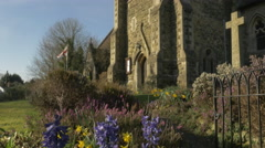4K Church Garden Bluebells Flowers Clock Tower Steeple Stone Cross Pan Up & Down Stock Footage