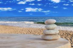 Balanced several Zen stones on blurred beautiful the beach background Stock Photos