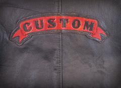 Red custom label on back of leather jacket in close-up. Stock Photos
