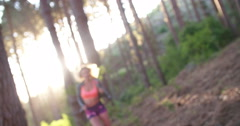 Woman athlete smiling in a forest with morning sunflare - stock footage