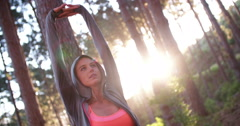 Athlete stretching with arms raised and eyes closed in forest - stock footage