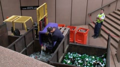 Bottles and glass recycling bin tipped into collection truck wide - stock footage