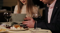 Lovely couple choosing some specialty from menu at restaurant. Stock Footage