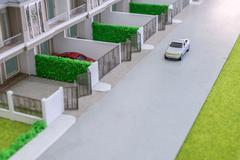 car toy on the road  in front of home model - stock photo