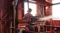 Woman working on textile machine indoors - Myanmar Stock Footage