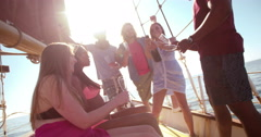 Mixed group of friends on yacht drinking champagne with sunflare - stock footage