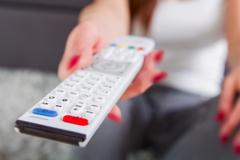Television remote control in woman hand. Unrecognizable person. Stock Photos