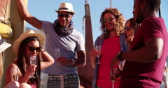 Long-haired man in sunglasses partying with friends on a yacht Stock Footage
