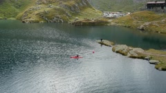 Aerial shot of a man paddling a canoe on a mountain lake Stock Footage