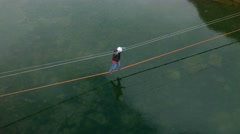 Close up aerial view of a man walking on a rope over a lake Stock Footage
