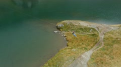 Aerial view of a person crossing a lake on the zipline Stock Footage